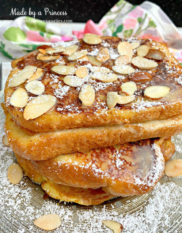 Sprinkle marzipan stuffed french toast with powdered sugar and toasted almonds and pour on the white chocolate sauce