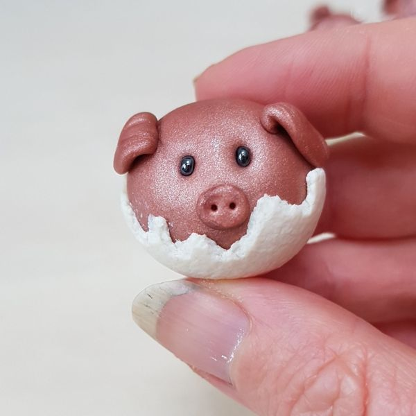 Pigs in blankets tree decor being held between thumb and finger for scale from madebymecrafts