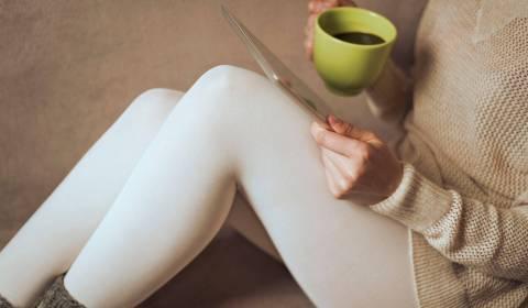 A woman sip a mug of coffee
