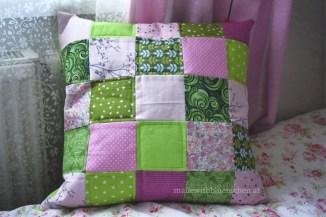 gruen-rosa Kissen vorm Fenster