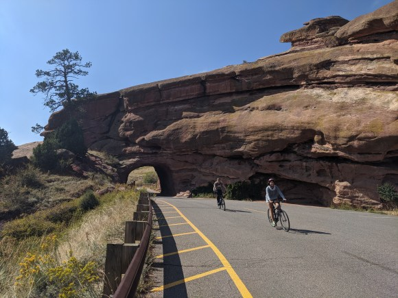 2 cyclists riding down the hill after passing through a tunnel at Red Rock Park in Colorado