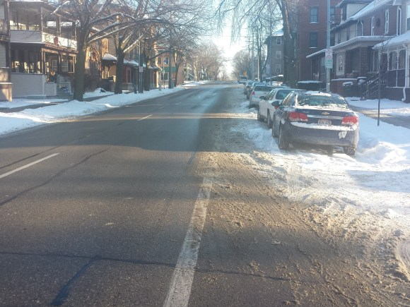 A snowy Madison street, badly cleared and with on-street parking