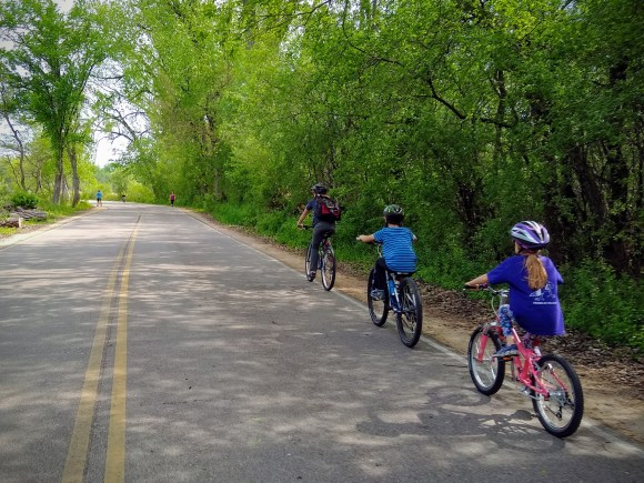 Two children and an adult biking on Arboretum Drive