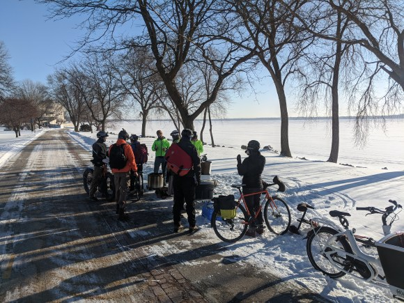 A group of people with bicycles on the Capital City Trail in Law Park. The lake is frozen and the ground covered in snow.
