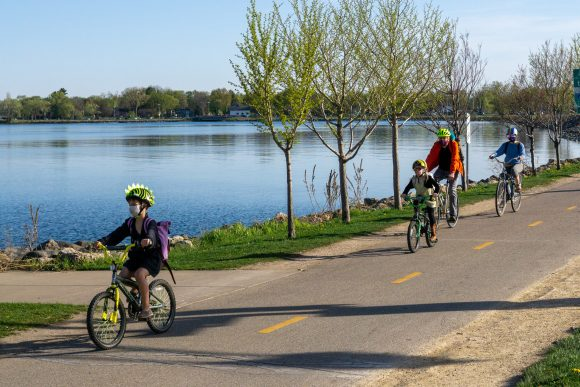 A group of children and adults biking on the Cap City Trail along Lake Monona