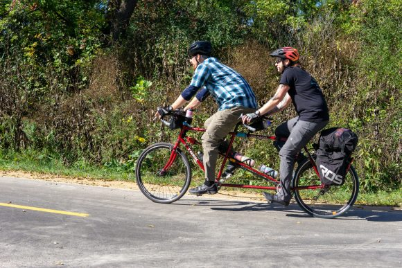 Two people riding a tandem bicycle on the Southwest Path