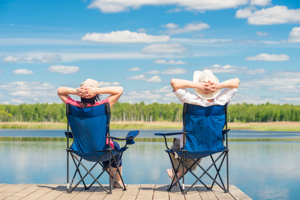 man and woman relaxing on the dock of a lake