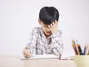 young asian boy writing frustruated angry head down-2015