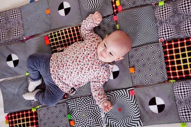 bebé tumbado boca arriba en manta de juegos