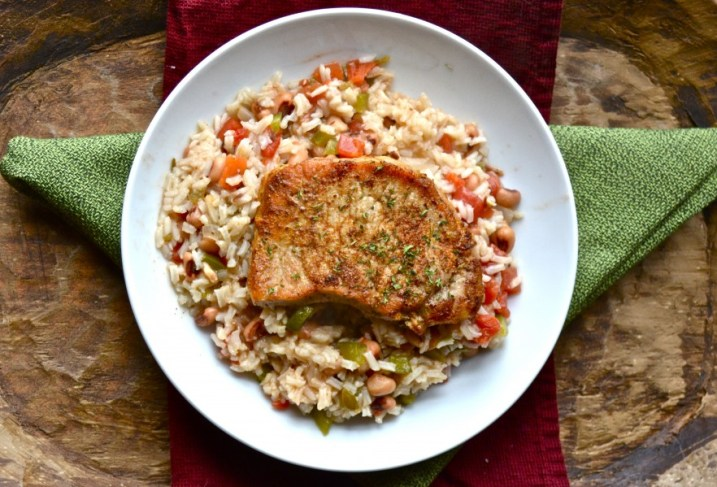 One Pan Pork Chops and Rice! Ultra tender pork chops on a bed of spicy rice and black eyed peas! Easy enough for a weeknight but fancy enough for a dinner party! A gluten free dinner!