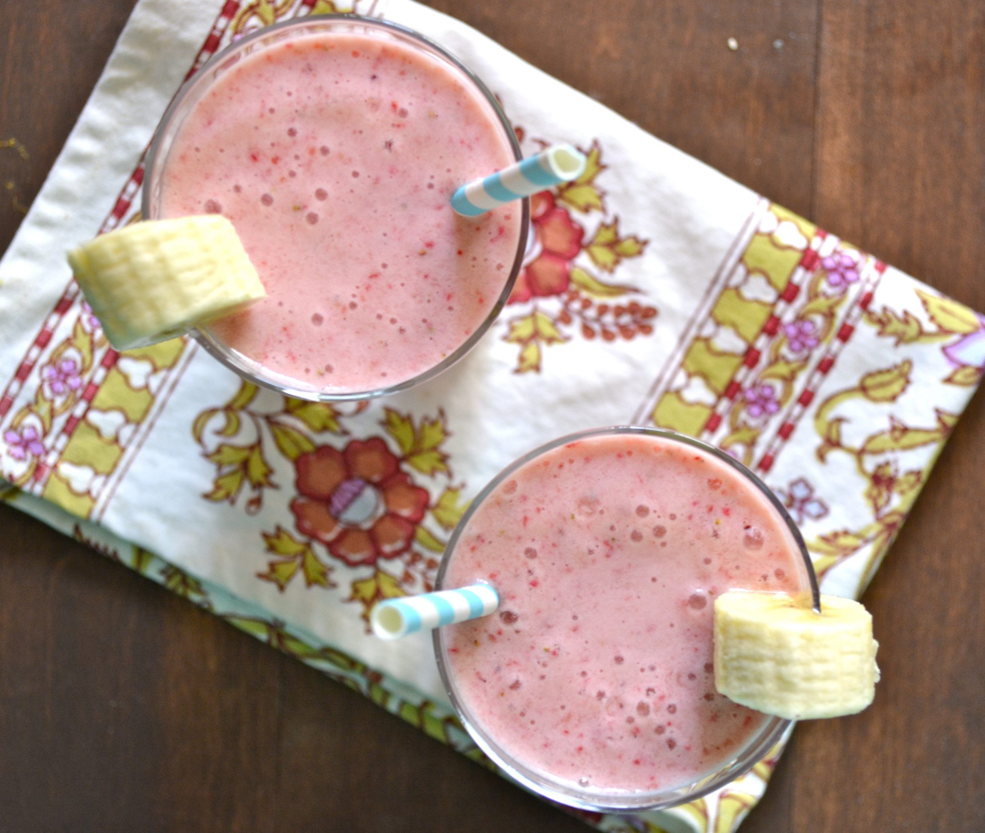 two glasses of strawberry and banana smoothie with straws
