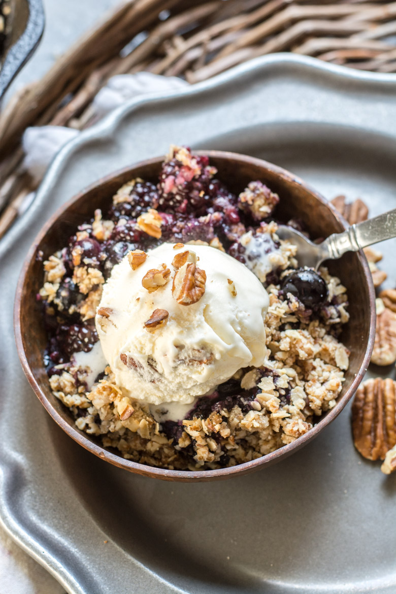 This Berry Crisp with Oatmeal Crumble Topping features warm, sweet blueberries and blackberries with a crisp oatmeal crumble topping! Top with ice cream for an ultra satisfying dessert!