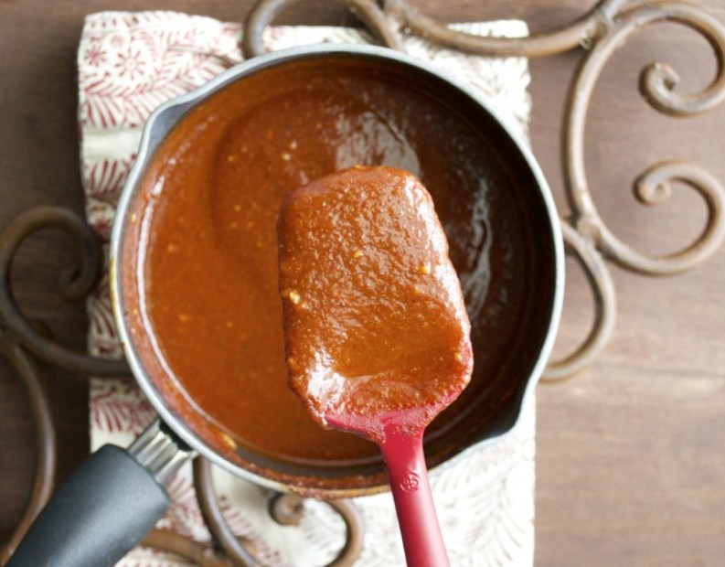 homemade red enchilada sauce in a saucepan with a spatula hovering over top