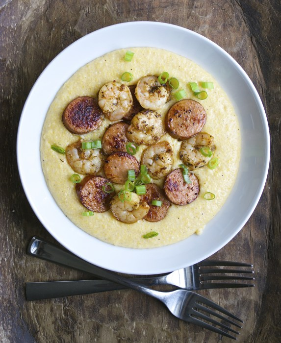 Jerk Shrimp and Andouille Sausage are cooked to perfection and laid on a bed of ultra creamy cheddar grits for the ultimate Southern meal!