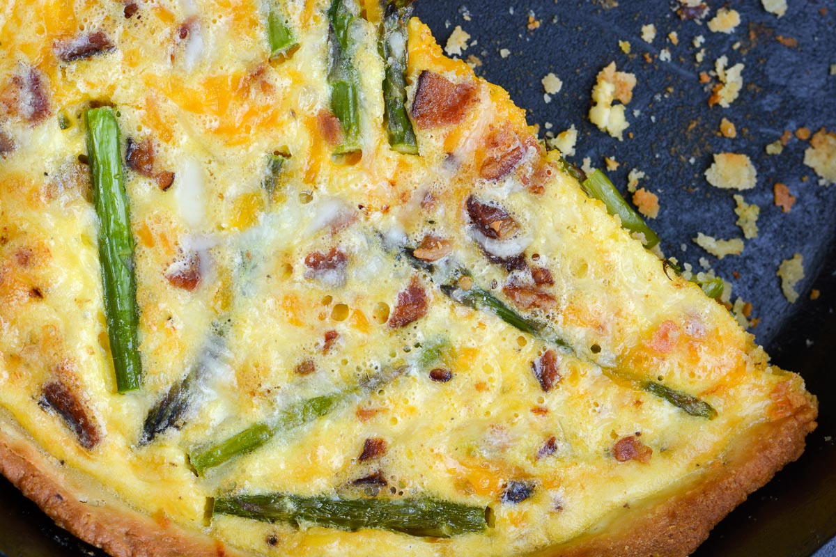 Overhead view of a bacon asparagus quiche in a cast iron skillet.
