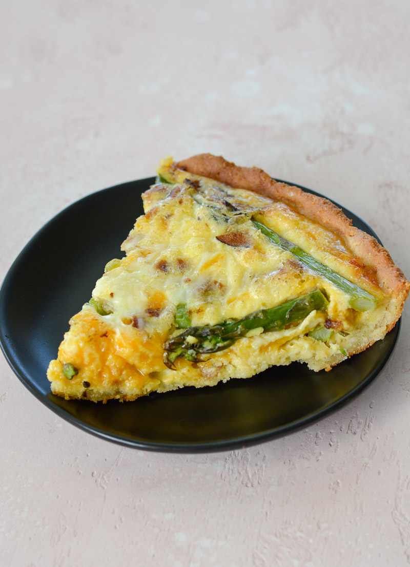 A slice of asparagus, bacon and cheddar quiche on a gray dessert plate.