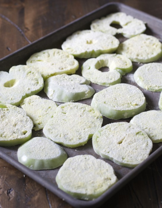 green tomato slices coated in breading on a baking tray
