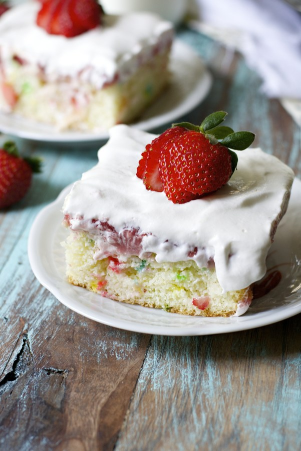 close up of a slice of strawberry funfetti cake on a white plate. Another cake slice is in the background.