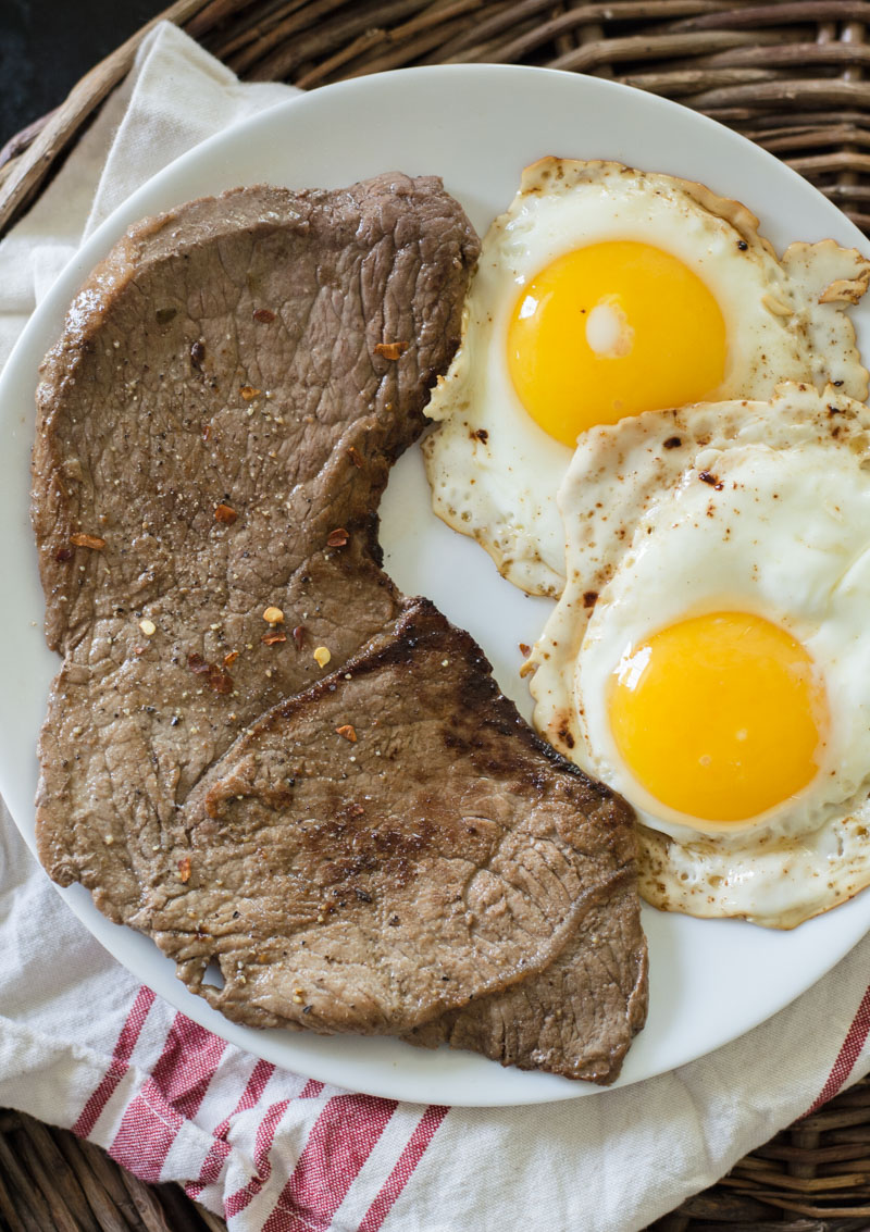 breakfast steak and eggs on a white plate