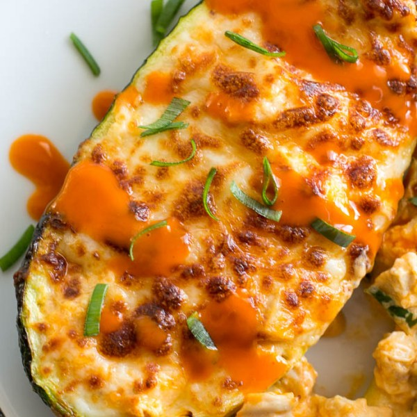Try these Keto Buffalo Chicken Zucchini Boats packed with tangy buffalo sauce, chicken and cheese! These zucchini boats are cooked in either an air fryer or oven for a delicious low carb meal! #keto