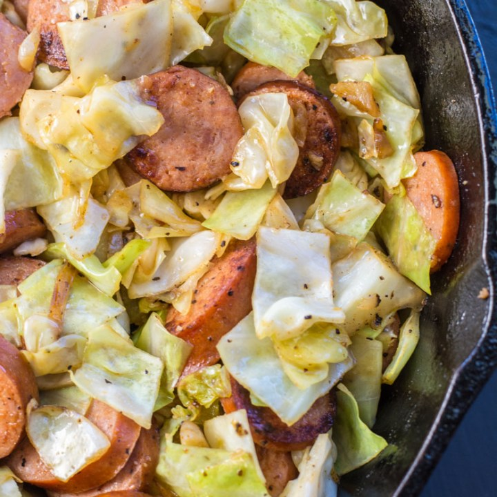 Need an easy low carb, one pan dinner? I've got you covered! This Keto Sausage and Cabbage Skillet is ready in under 20 minutes and has less than 6 carbs per serving! #keto #onepan