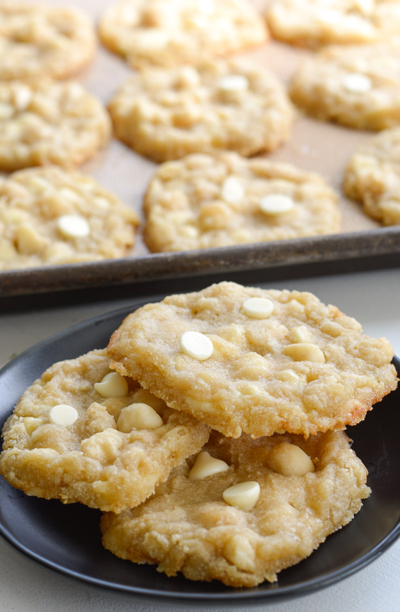 three keto macadamia nut cookies on a small plate. extra cookies are on a baking sheet in the background.