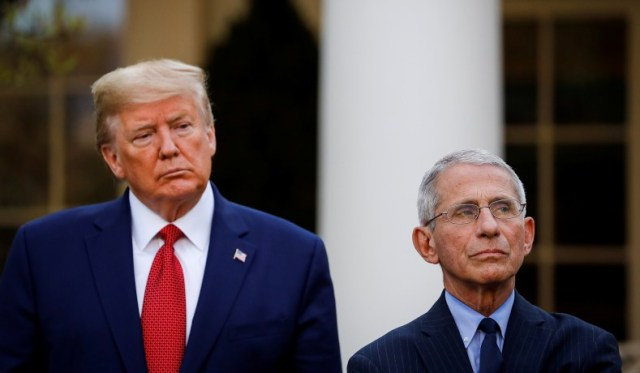 U.S. President Donald Trump and NIH National Institute of Allergy and Infectious Diseases Director Anthony Fauci listen during a news conference in the Rose Garden of the White House in Washington, U.S., March 29, 2020. (Al Drago/Reuters)