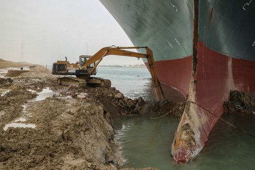 """25 March 2021, Egypt, Suez: An excavator attempts to free the front end of the """"Ever Given"""", a container ship operated by the Evergreen Marine Corporation. AP Images"""
