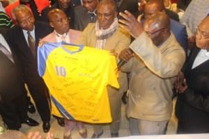 Sous le regard de Mokili Saio, Bonga Bonga, Eloni, Kakoko, Mayele, et de leurs collègues,  Ricky Kibuaka présente  au capitaine le tricot portant son numéro légendaire avec les couleurs du drapeau de la RDC.