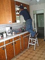 Attila installing locks on the kitchen window at the little house, August 1, 2010.