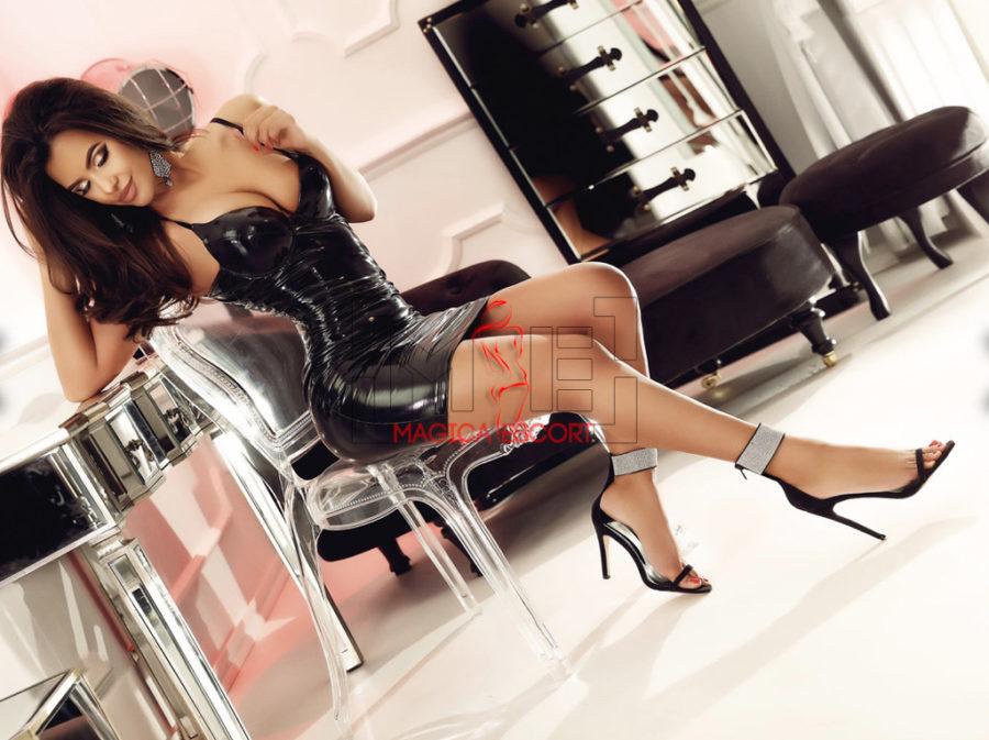 Aisha top model russa in abitino sexy di pelle e sandali dal tacco altissimo.