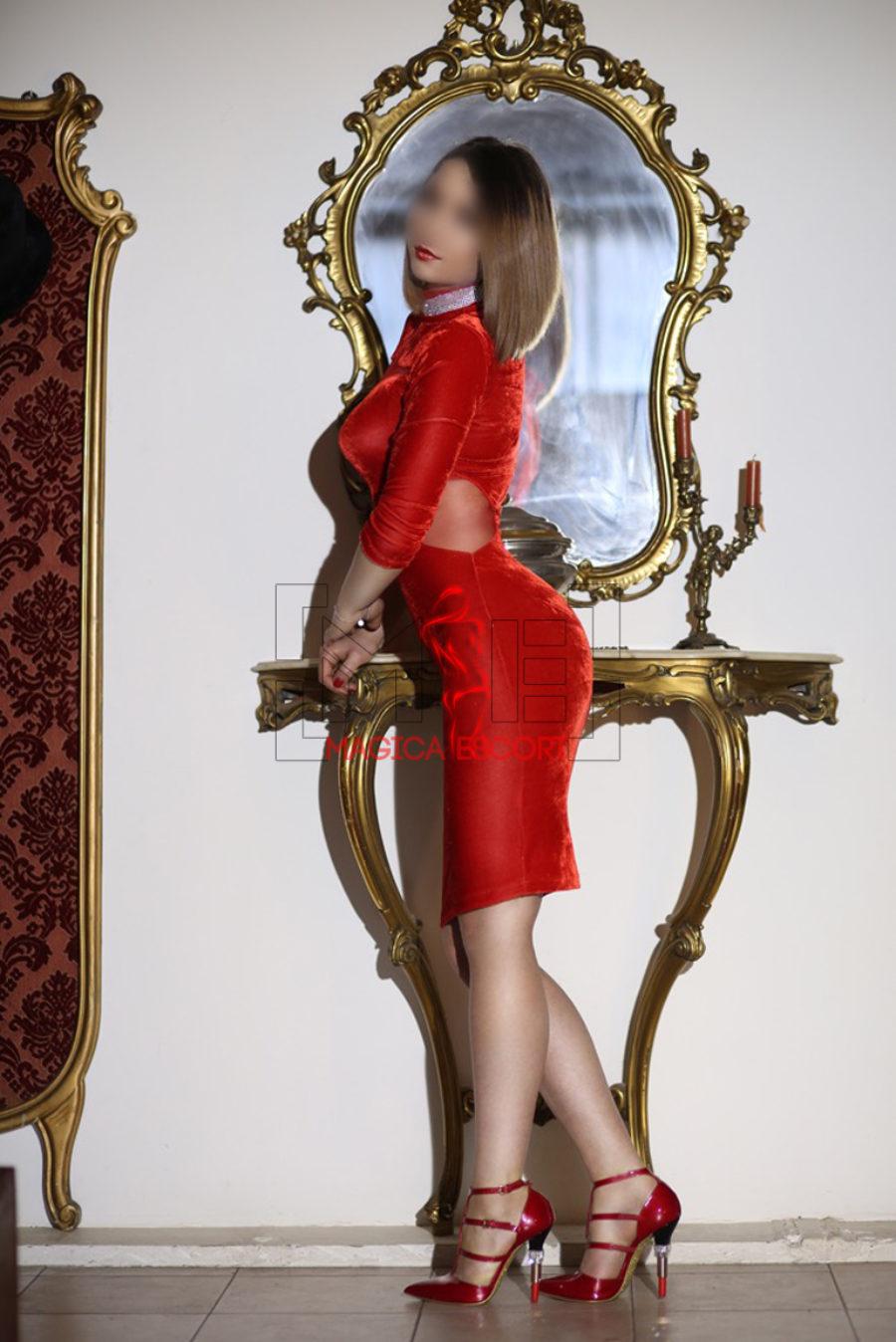 Agatha escort Milano indossa un abito elegante color rosso fuoco.