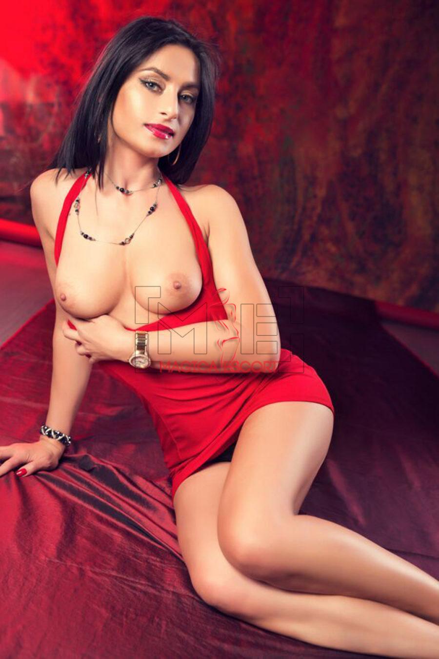 Il seno bellissimo di Anastasia escort Milano fasciata in un abitino rosso fuoco.