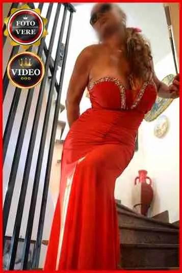 Daisy escort Roma indossa uno splendido abito da sera rosso fuoco per la foto di anteprima del suo annuncio personale per incontri.