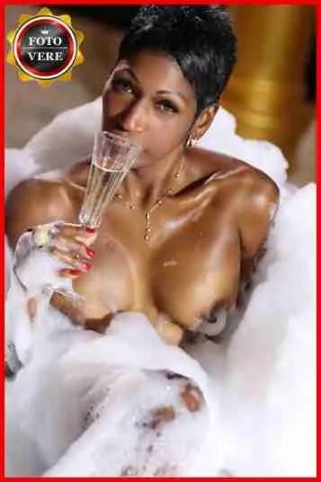 Escort cubana Sharon nella vasca da bagno mentre sorseggia dello champagne. Magica Escort.