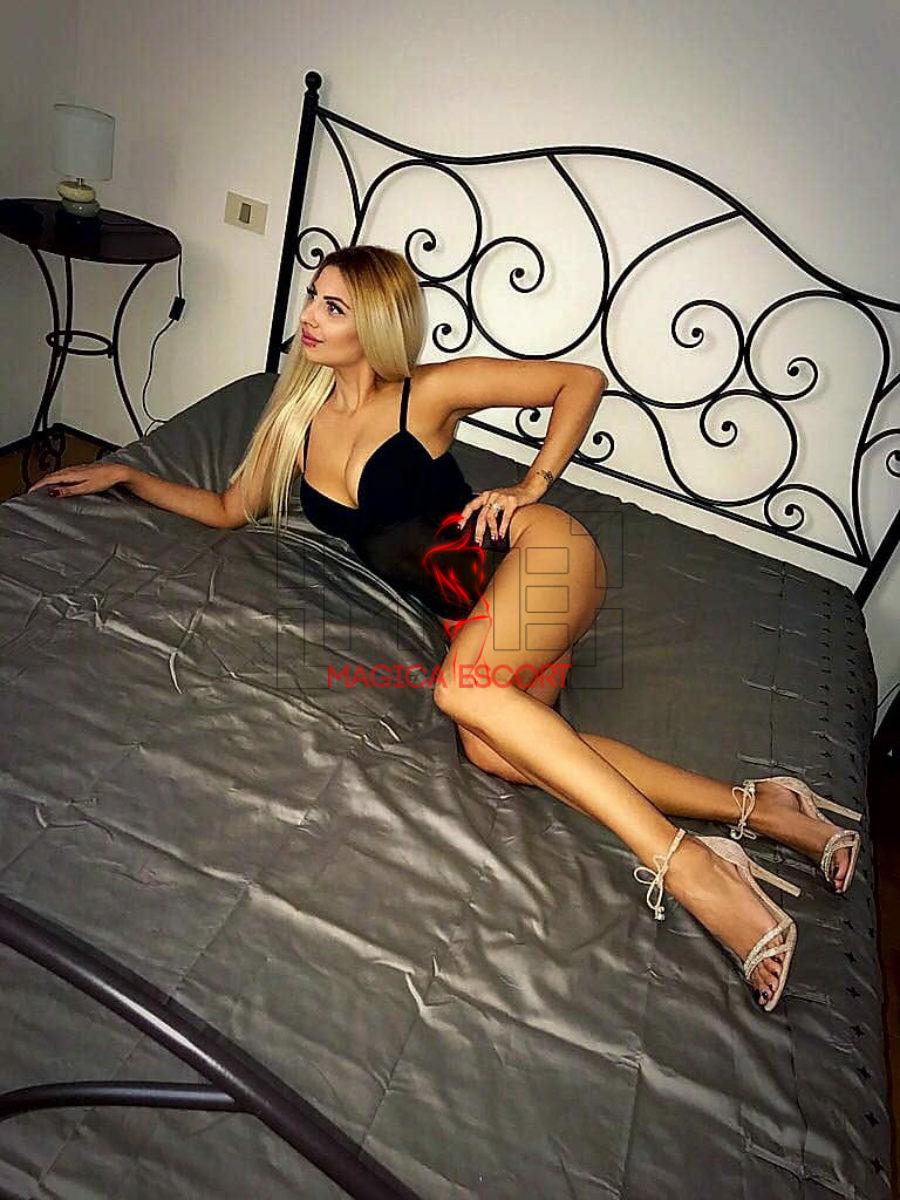 Model top class Erica distesa nel suo letto con una guepière nera. Magica Escort.