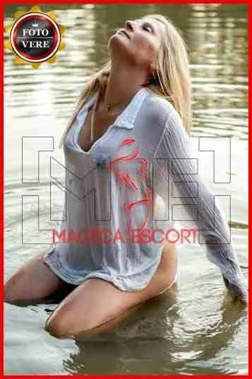 Monika accompagnatrice Brescia inginocchiata nell'acqua con la camicia trasparente. Magica Escort
