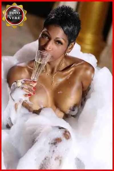 Escort cubana Sharon nella vasca da bagno mentre sorseggia dello champagne. Magica Escort