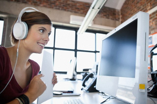 Young woman working on computer and listening to music in office --- Image by © Olix Wirtinger/Corbis