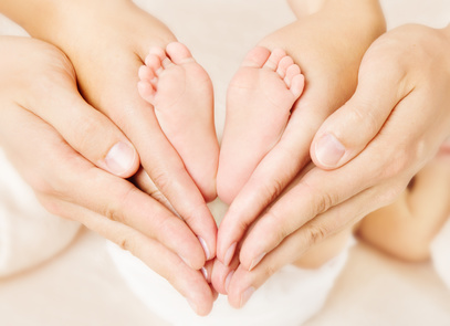 Newborn baby feet parents holding in hands. Love simbol as heart sign.