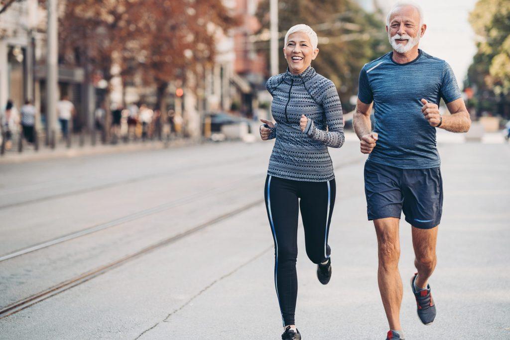 Um homem e uma mulher correndo lado a lado na rua