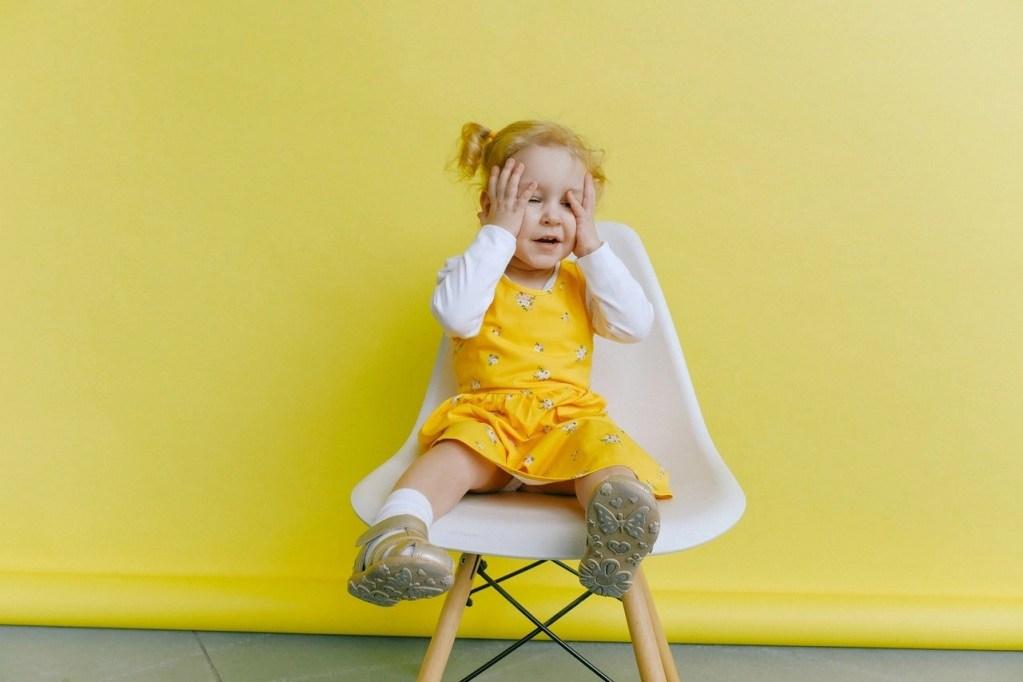 момиченце, седнало на стол, хванало се за главата