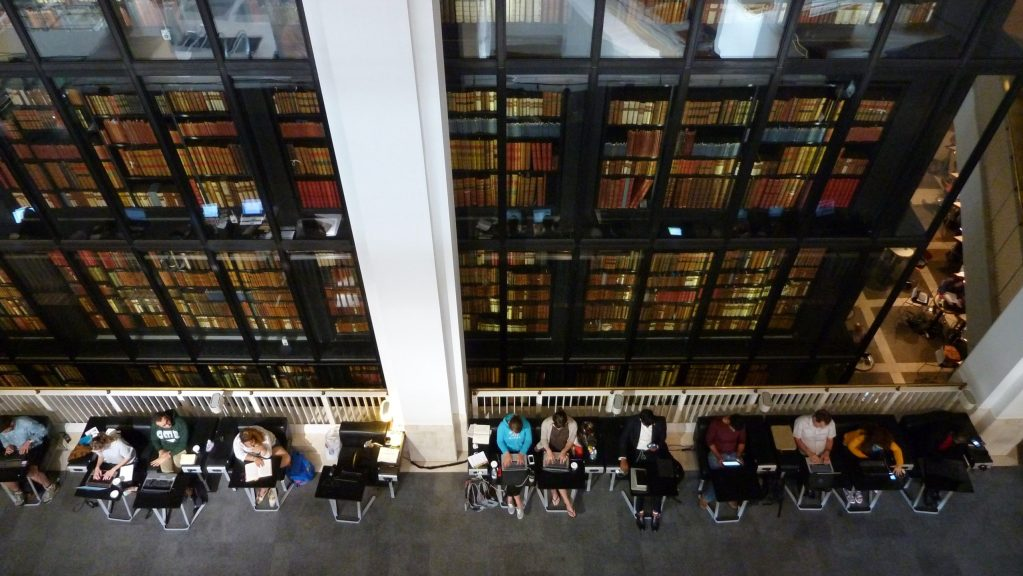 People studying at the British Library with a small selection of books behind them