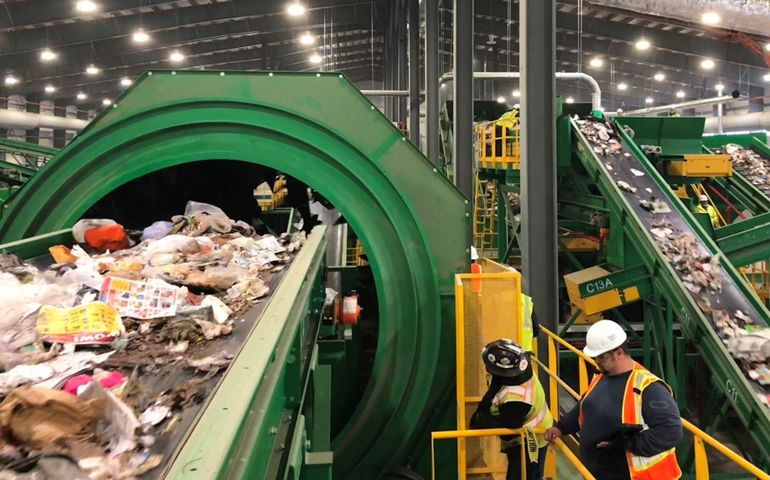 the interior of a large building with a lot of conveyor belts, including a closeup of one with garbage and a man with a hardhat on a ladder