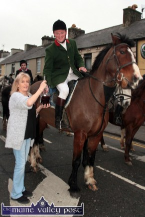 A Drop for the Huntsman: Kerry Hunt Club Huntsman, Fred O'Connor taking the traditional glass of Mulled Wine from publican, Kathleen O'Connor outside The Half Barrel on Sunday afternoon. ©Photograph: John Reidy
