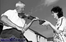 Passing it on: The late Scartaglin fiddler, Mikey Duggan playing a tune for a collector at the annual feile in the village. ©Photograph: John Reidy 5-8-1995