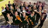 In Harmony: The entire Scartaglin National School orchestra posing with their model fiddles in preparation for their exhibition at their village heritage centre for next weekend's World Fiddle Day celebrations. ©Photograph: John Reidy
