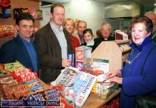 Service with a smile: Rugby star Mick Galwey joined his sister, Frances and her husband Tim McCarthy (left) at the check-out of their Currow supermarket on Sunday morning. Included are: Mary Butler with Michael and Michelle Cunningham and Fr. Pat Sugrue. ©Photograph: John Reidy 8-12-2002