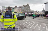 Sgt. John O'Mahony removes his cap in a salute to a good friend and 'a sound man' as the remains of Georgie O'Callaghan are shouldered onto Main Street in Castleisland last April. ©Photograph: John Reidy 19-4-2018
