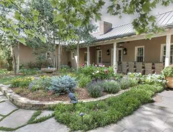 Courtyard Area Landscape Design Prosper Texas residence with stone masonry landscape border, flagstone walkway and Texas native plants in backyard outdoor living area.